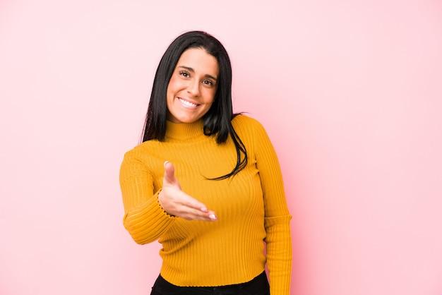 Jovem mulher caucasiana isolada em um fundo rosa, esticando a mão na câmera em gesto de saudação.