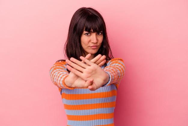 Jovem mulher caucasiana isolada em um fundo rosa fazendo um gesto de negação