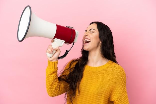 Jovem mulher caucasiana isolada em um fundo rosa gritando em um megafone para anunciar algo em posição lateral