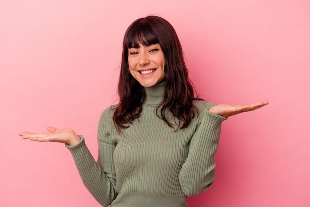 Jovem mulher caucasiana isolada em um fundo rosa, mostrando uma expressão de boas-vindas.
