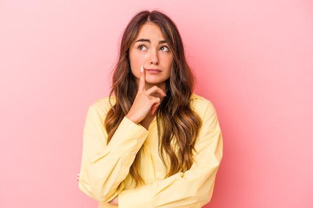 Jovem mulher caucasiana isolada em um fundo rosa, olhando de soslaio com expressão duvidosa e cética.