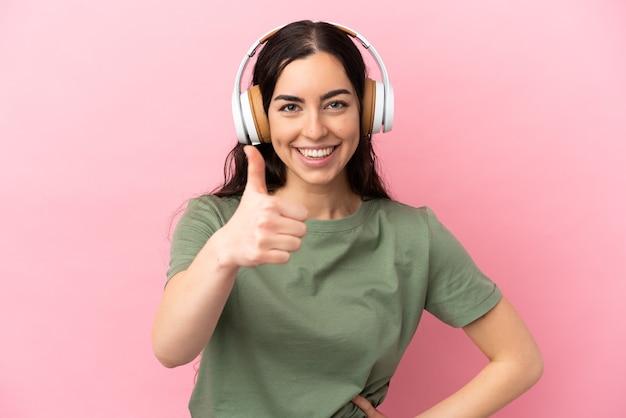 Jovem mulher caucasiana isolada em um fundo rosa ouvindo música e com o polegar para cima