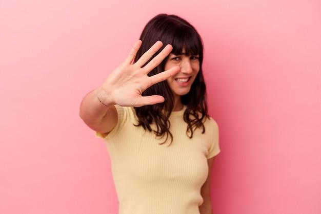 Jovem mulher caucasiana isolada em um fundo rosa, rejeitando alguém mostrando um gesto de nojo.
