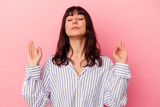 Jovem mulher caucasiana isolada em um fundo rosa relaxa após um árduo dia de trabalho, ela está realizando ioga.