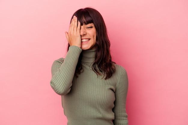 Jovem mulher caucasiana isolada em um fundo rosa, se divertindo, cobrindo metade do rosto com a palma da mão.