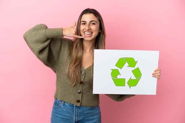Jovem mulher caucasiana isolada em um fundo rosa segurando um cartaz com o ícone de reciclagem e fazendo gestos de telefone