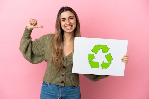 Jovem mulher caucasiana isolada em um fundo rosa segurando um cartaz com o ícone de reciclagem e um gesto orgulhoso