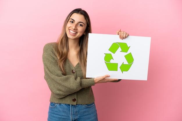 Jovem mulher caucasiana isolada em um fundo rosa segurando um cartaz com o ícone de reciclagem e uma expressão feliz