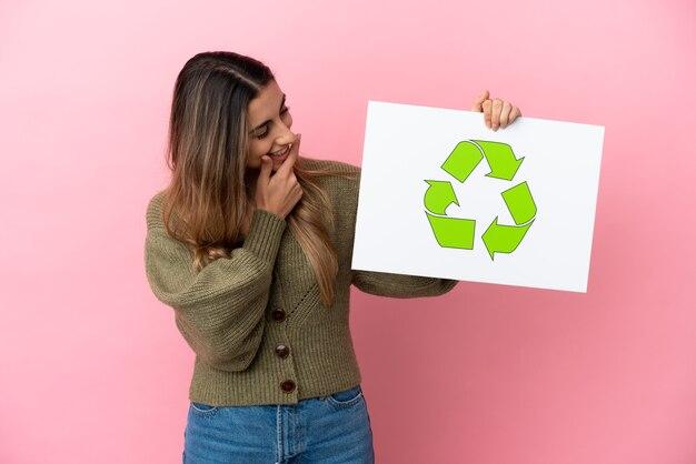 Jovem mulher caucasiana isolada em um fundo rosa segurando um cartaz com o ícone de reciclagem
