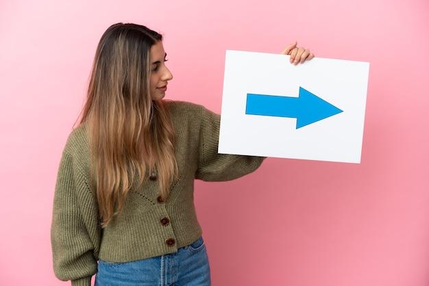 Jovem mulher caucasiana isolada em um fundo rosa segurando um cartaz com o símbolo de seta