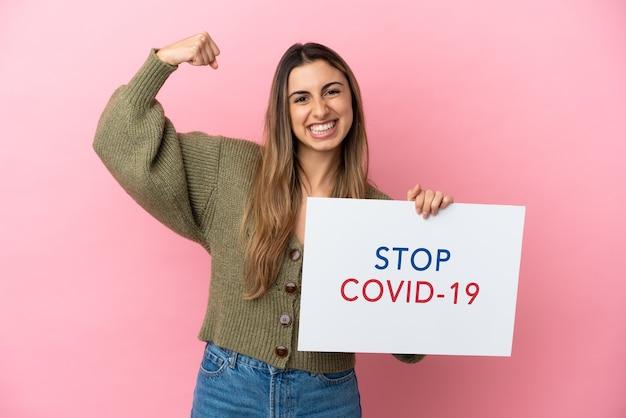 Jovem mulher caucasiana isolada em um fundo rosa segurando um cartaz com o texto pare covid 19 e fazendo um gesto forte