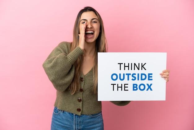 Jovem mulher caucasiana isolada em um fundo rosa segurando um cartaz com o texto pense fora da caixa e gritando