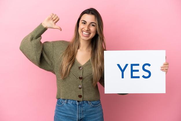 Jovem mulher caucasiana isolada em um fundo rosa segurando um cartaz com o texto sim com gesto orgulhoso