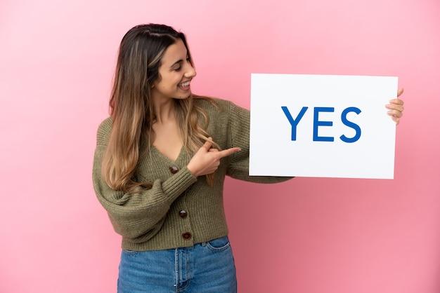 Jovem mulher caucasiana isolada em um fundo rosa segurando um cartaz com o texto sim e apontando-o
