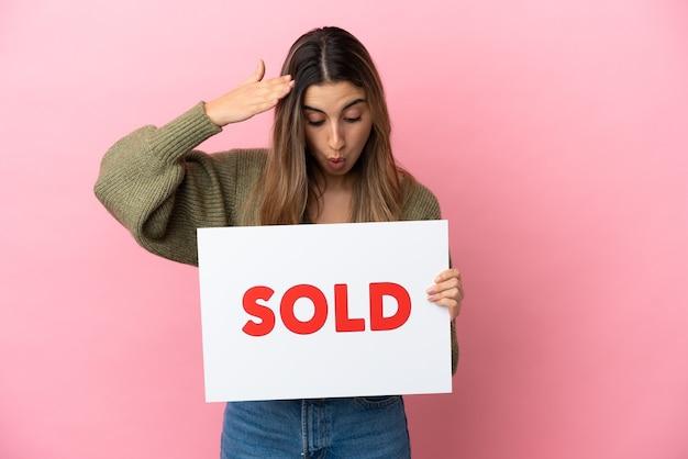 Jovem mulher caucasiana isolada em um fundo rosa segurando um cartaz com o texto vendido com expressão de surpresa