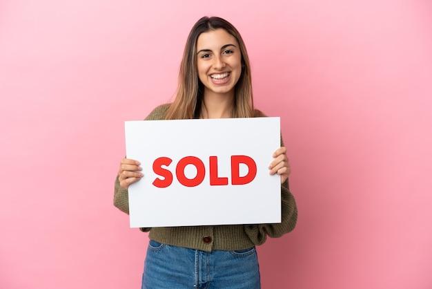 Jovem mulher caucasiana isolada em um fundo rosa segurando um cartaz com o texto vendido com uma expressão feliz