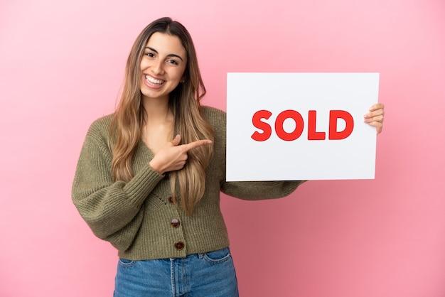 Jovem mulher caucasiana isolada em um fundo rosa segurando um cartaz com o texto vendido e apontando-o