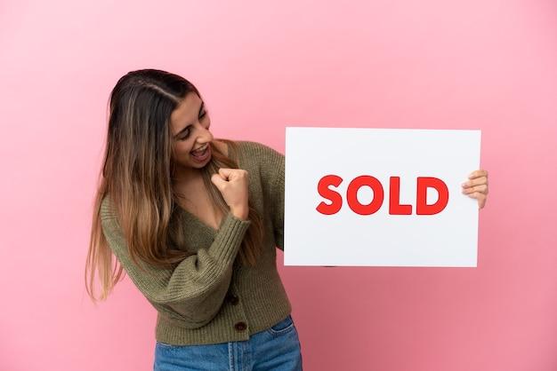 Jovem mulher caucasiana isolada em um fundo rosa segurando um cartaz com o texto vendido e comemorando uma vitória