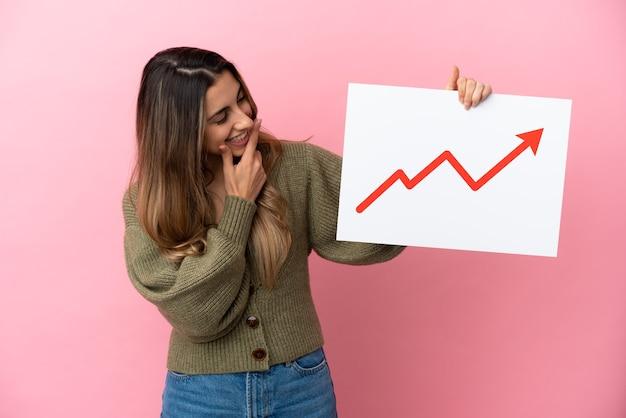 Jovem mulher caucasiana isolada em um fundo rosa segurando uma placa com um símbolo de seta de estatísticas crescentes e pensando