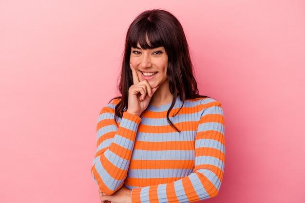 Jovem mulher caucasiana isolada em um fundo rosa, sorrindo feliz e confiante, tocando o queixo com a mão.