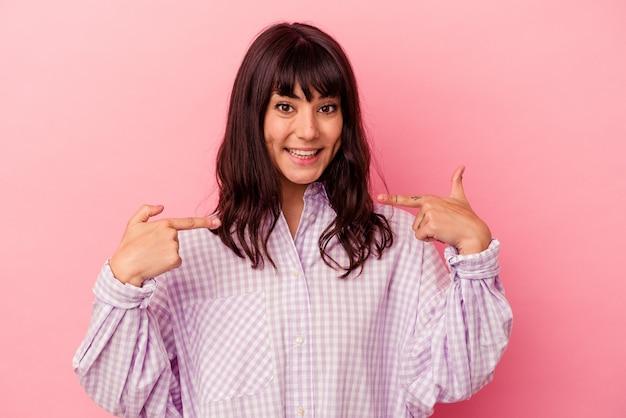 Jovem mulher caucasiana isolada em um fundo rosa surpresa apontando com o dedo, sorrindo amplamente.