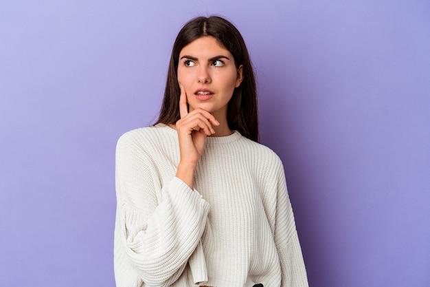 Jovem mulher caucasiana, isolada em um fundo roxo, contemplando, planejando uma estratégia, pensando na forma de um negócio.