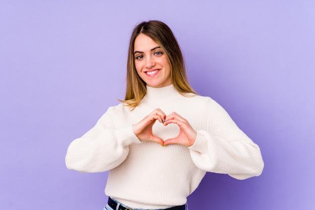 Jovem mulher caucasiana isolada em um fundo roxo, sorrindo e mostrando uma forma de coração com as mãos.
