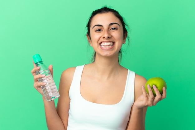 Jovem mulher caucasiana isolada em um fundo verde com uma maçã e uma garrafa de água