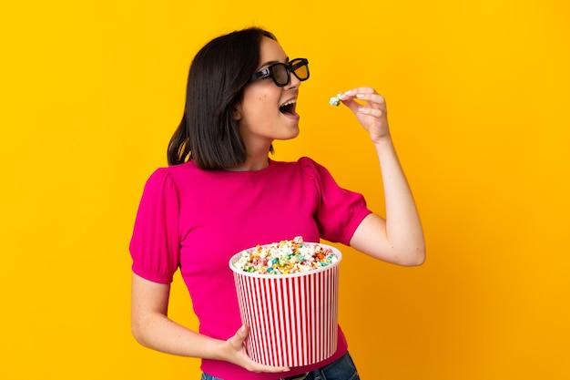 Jovem mulher caucasiana isolada em uma parede amarela com óculos 3d e segurando um grande balde de pipocas