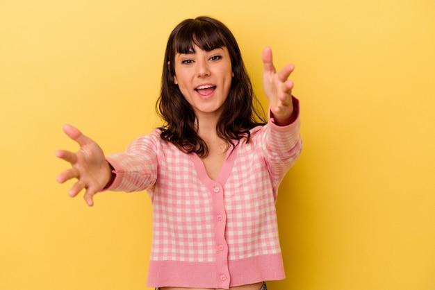 Jovem mulher caucasiana isolada em uma parede amarela se sente confiante dando um abraço na frente