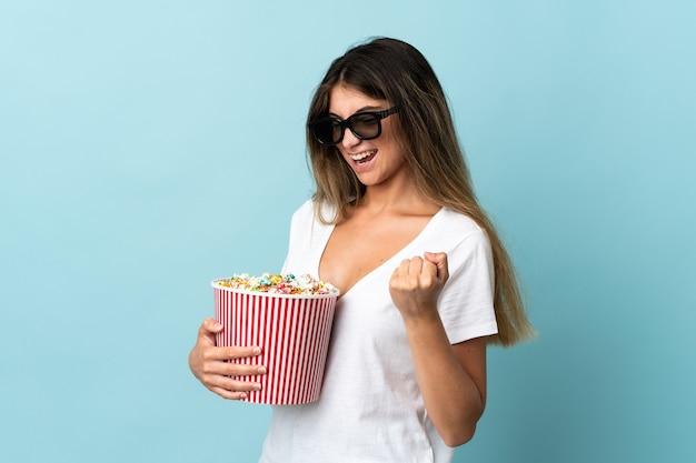 Jovem mulher caucasiana isolada em uma parede azul com óculos 3d e segurando um grande balde de pipocas enquanto olha para o lado