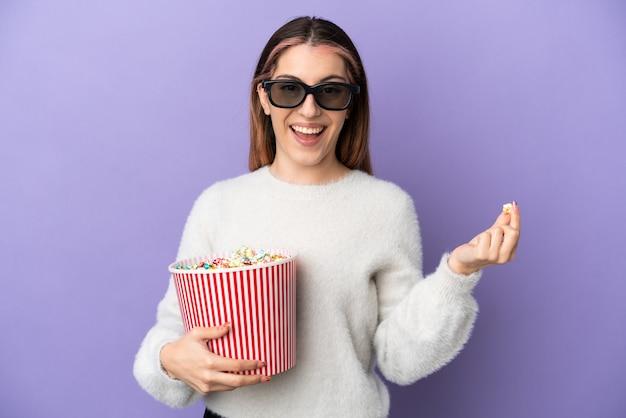 Jovem mulher caucasiana isolada em uma parede azul com óculos 3d e segurando um grande balde de pipocas