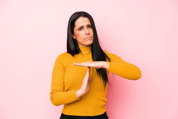 Jovem mulher caucasiana isolada em uma parede rosa, mostrando um gesto de tempo limite.