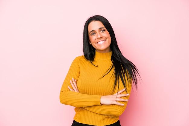 Jovem mulher caucasiana isolada em uma parede rosa que se sente confiante, cruzando os braços com determinação.