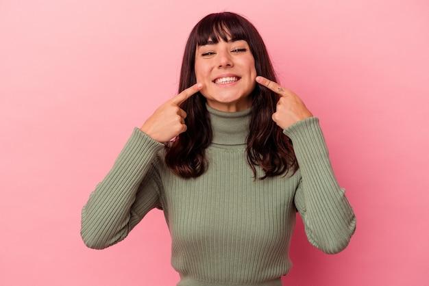 Jovem mulher caucasiana isolada em uma parede rosa sorrindo, apontando o dedo para a boca