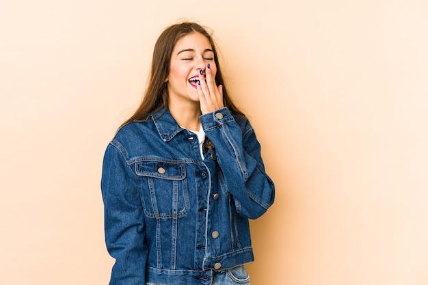 Jovem mulher caucasiana isolada en bege parede rindo de emoção feliz, despreocupada e natural.