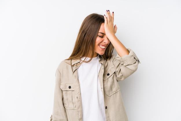 Jovem mulher caucasiana isolada esquecendo algo, batendo na testa com a palma e fechando os olhos.