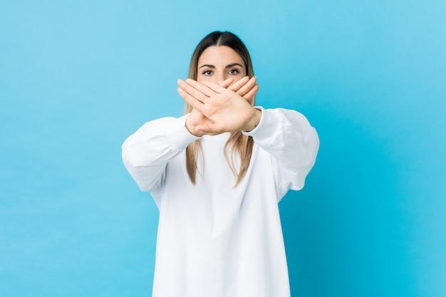 Jovem mulher caucasiana isolada fazendo um gesto de negação