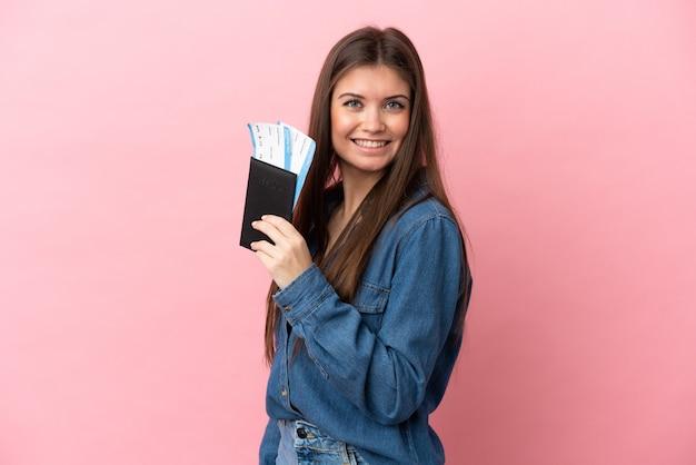 Jovem mulher caucasiana isolada feliz de férias com passaporte e passagens aéreas