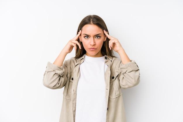 Jovem mulher caucasiana isolada focada em uma tarefa, mantendo os dedos apontando a cabeça.