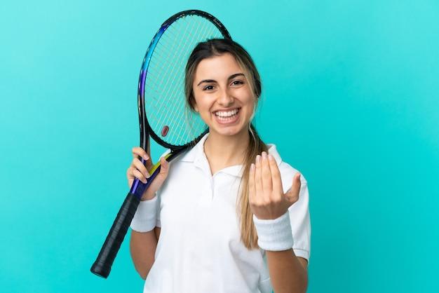 Jovem mulher caucasiana isolada jogando tênis e fazendo gestos de aproximação