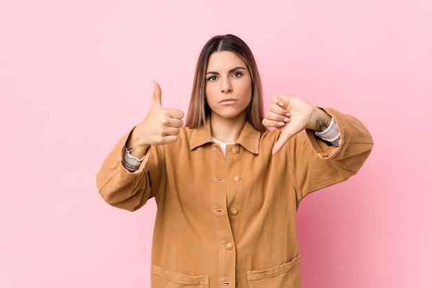 Jovem mulher caucasiana isolada mostrando os polegares para cima e os polegares para baixo