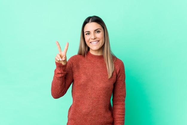 Jovem mulher caucasiana isolada mostrando sinal de vitória e sorrindo amplamente.
