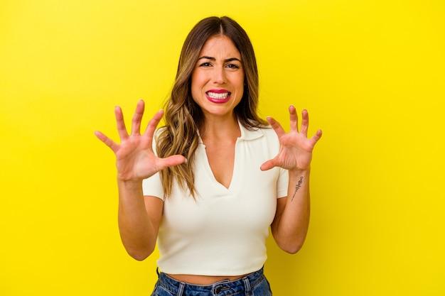 Jovem mulher caucasiana, isolada na parede amarela, mostrando garras imitando um gato, gesto agressivo.
