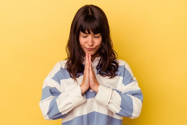 Jovem mulher caucasiana isolada na parede amarela orando, mostrando devoção, pessoa religiosa em busca de inspiração divina.