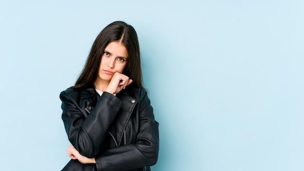 Jovem mulher caucasiana isolada na parede azul cansada de uma tarefa repetitiva.