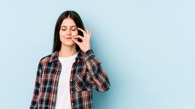 Jovem mulher caucasiana isolada na parede azul com os dedos nos lábios, mantendo um segredo.