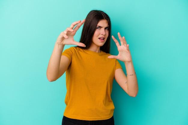Jovem mulher caucasiana isolada na parede azul, mostrando garras imitando um gato, gesto agressivo.