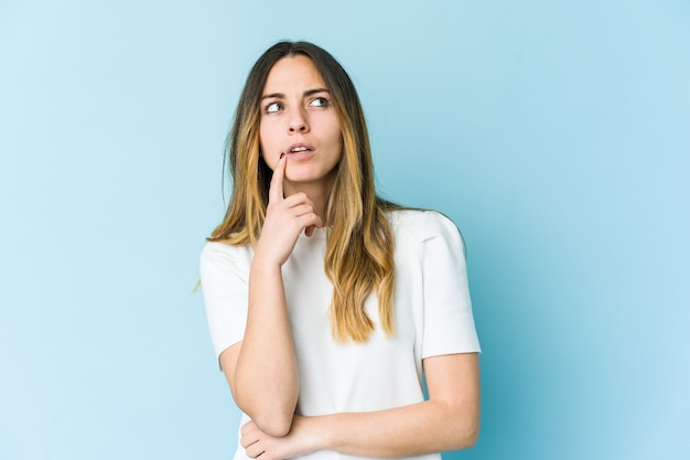 Jovem mulher caucasiana isolada na parede azul, olhando de soslaio com expressão duvidosa e cética.