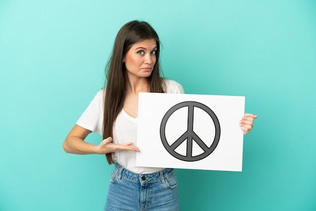 Jovem mulher caucasiana isolada na parede azul segurando um cartaz com o símbolo da paz e apontando-o